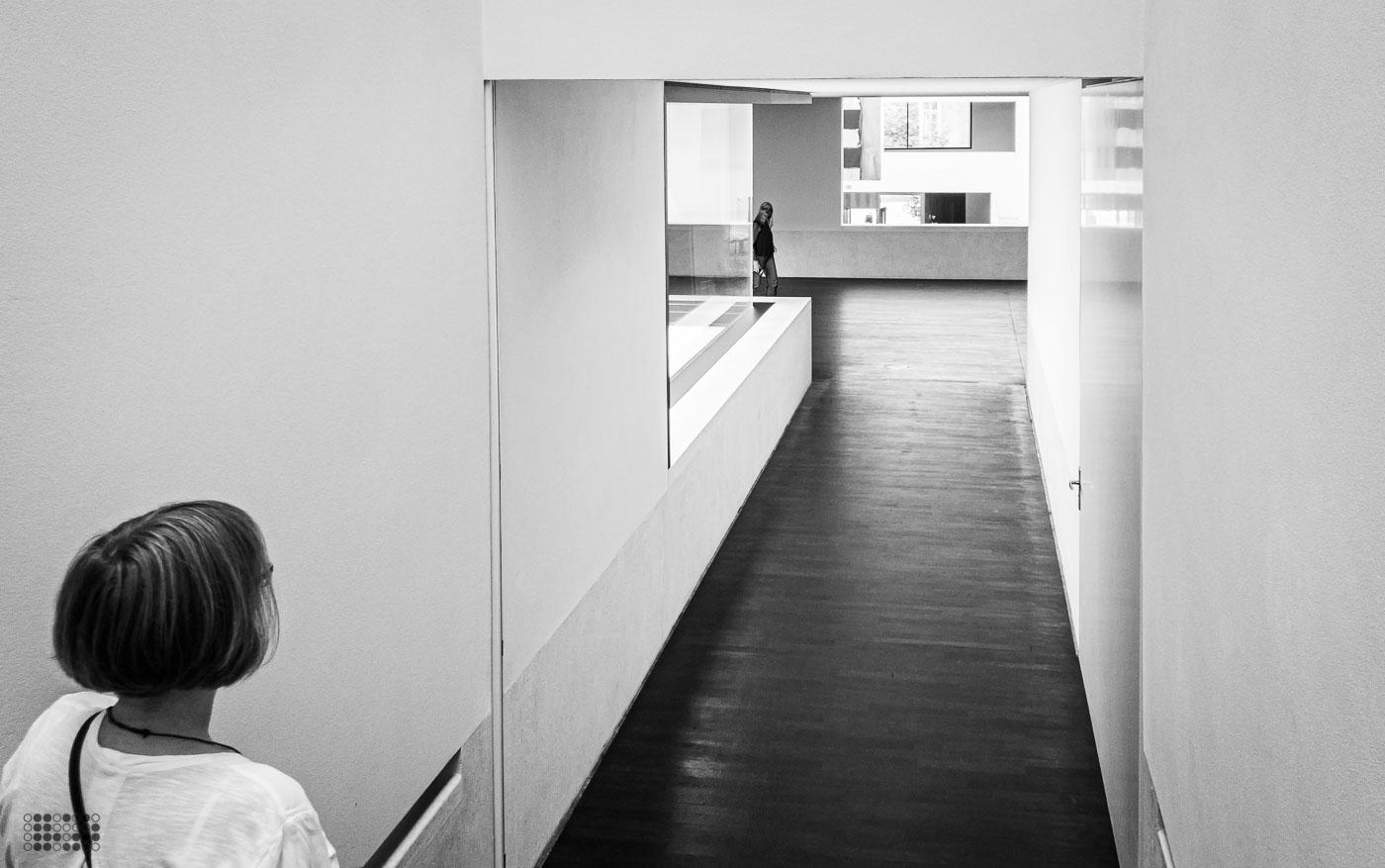 Blick über die Schulter einer Frau einen Gang in einem Museum hinab.