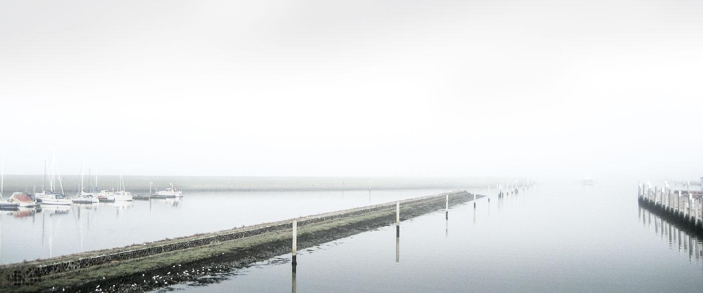 Eine hafenausfahrt im dichten Nebel.
