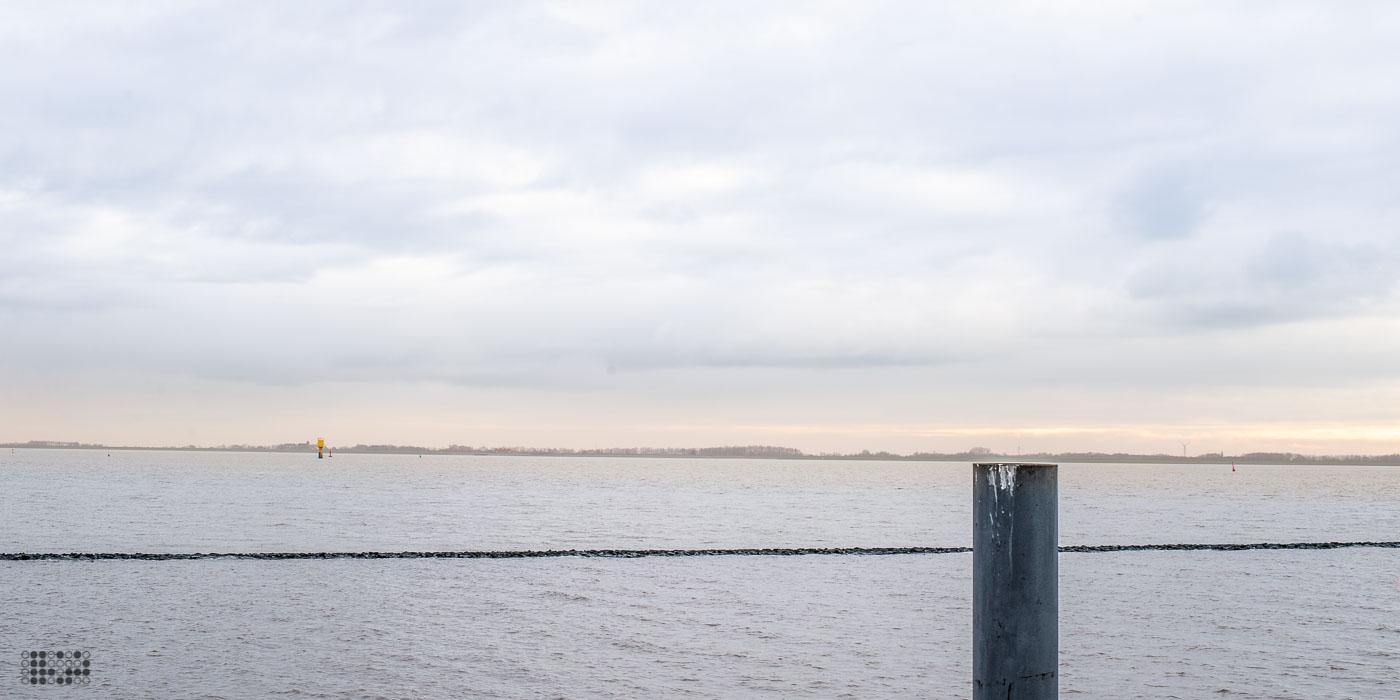 Blick auf die Ems-Mündung vor Emden. Vorne ein Holzpfahl, dahinter Nordsee, ganz hinten die hollädische Küste.